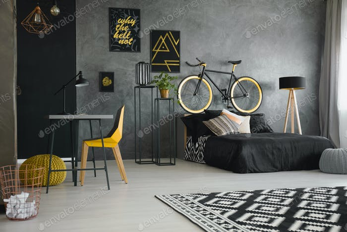 Real photo of a black bed standing against raw, gray wall in mod