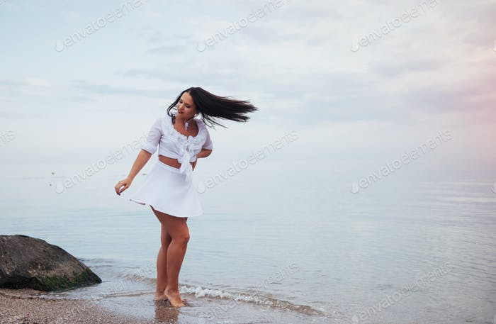 woman in a white shirt and skirt dancing barefoot