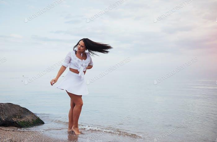 Frau in einem weißen Hemd und Rock tanzen barfuß