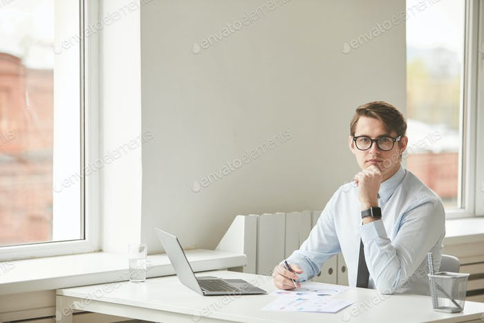 Young Professional at Desk in White Office Copy Space
