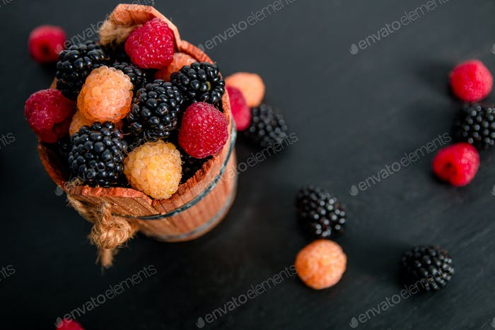 Mixed of red, black, yellow raspberries in a basket