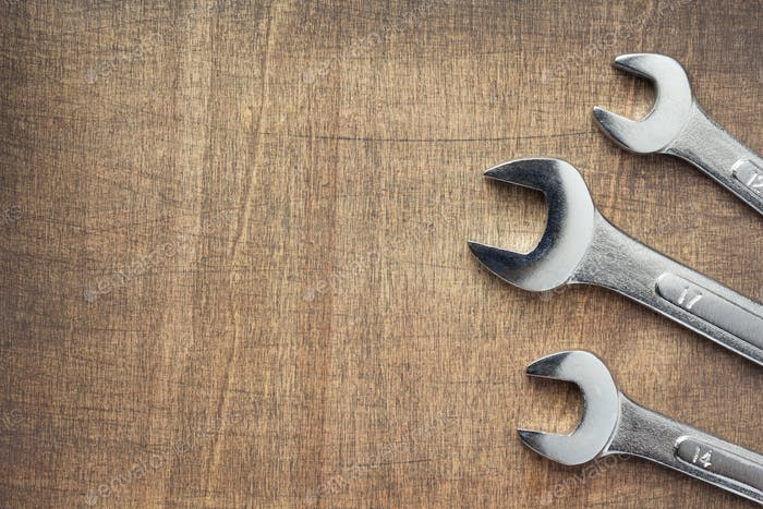 wrench tools at wooden background