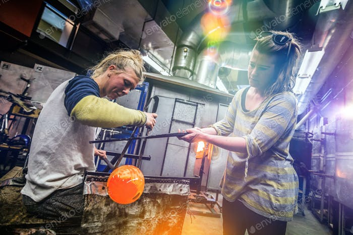 Two Blowing Glass Artists Finishing a Piece.
