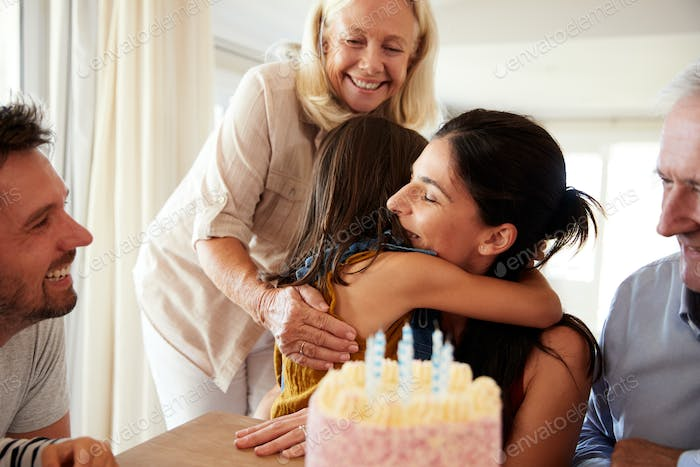 Mid adult woman embracing her daughter after blowing out candles on birthday cake, close up