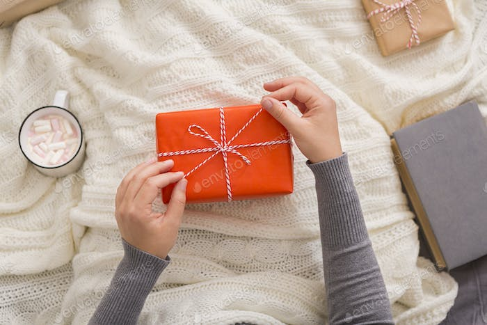 Woman drinking hot cocoa and opening presents
