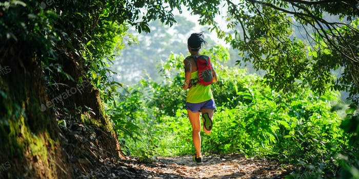 Woman cross country runner running in tropical forest trail