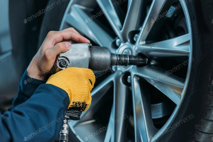 Abgeschnittener Schuss von automechanischen Abschrauben von Reifenschrauben an einem angehobenen Auto in einer Werkstatt.
