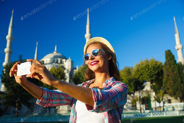 Girl in the hat making selfie by the smartphone on the backgroun