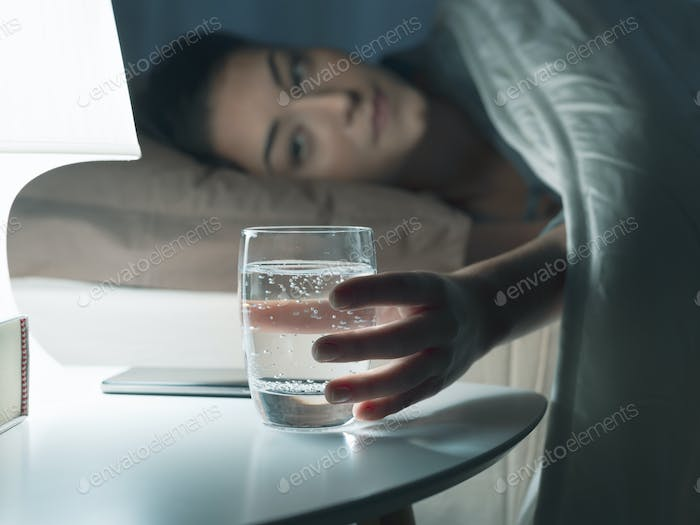 Woman drinking a glass of water at night