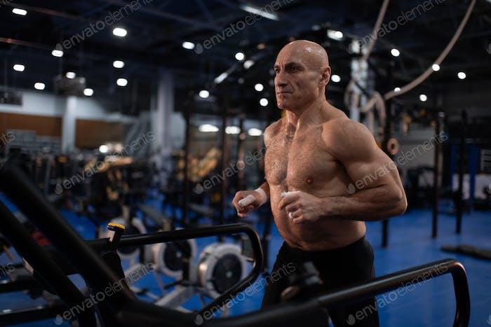 Muskulöser Senior Sportler läuft auf Laufband