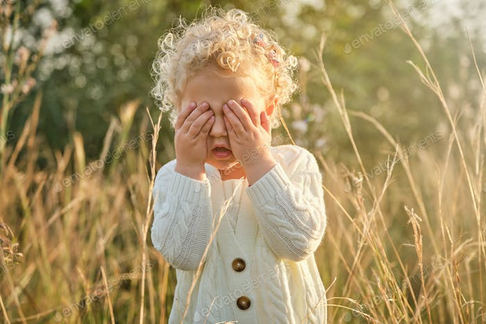 Funny little girl covering eyes with hands in nature
