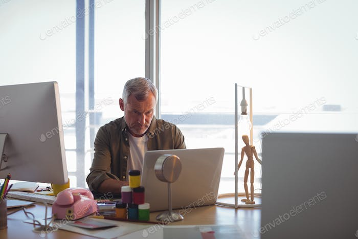 Focused businessman working on laptop at office