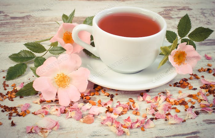 Vintage photo, Cup of tea with wild rose flower on old rustic board