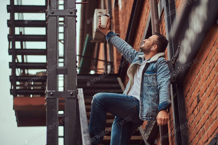 A handsome stylish man wearing a denim jacket holding a takeaway coffee on stairs outside.