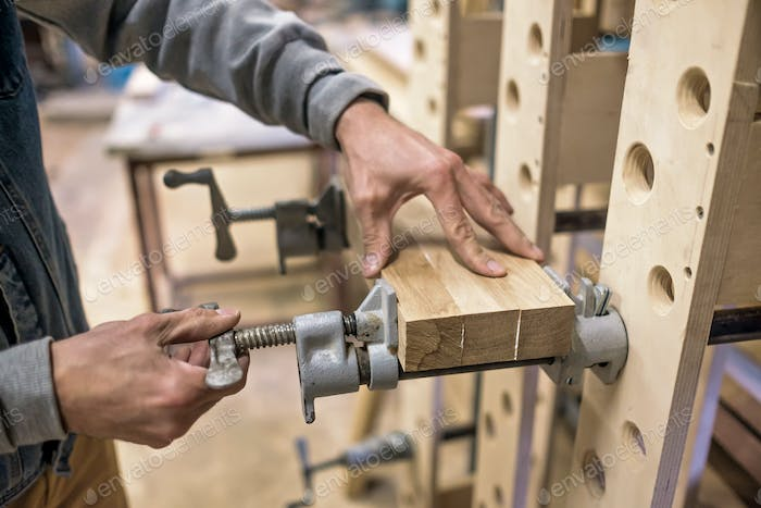 Using clamps and glue to connect wooden timbers for furniture detail