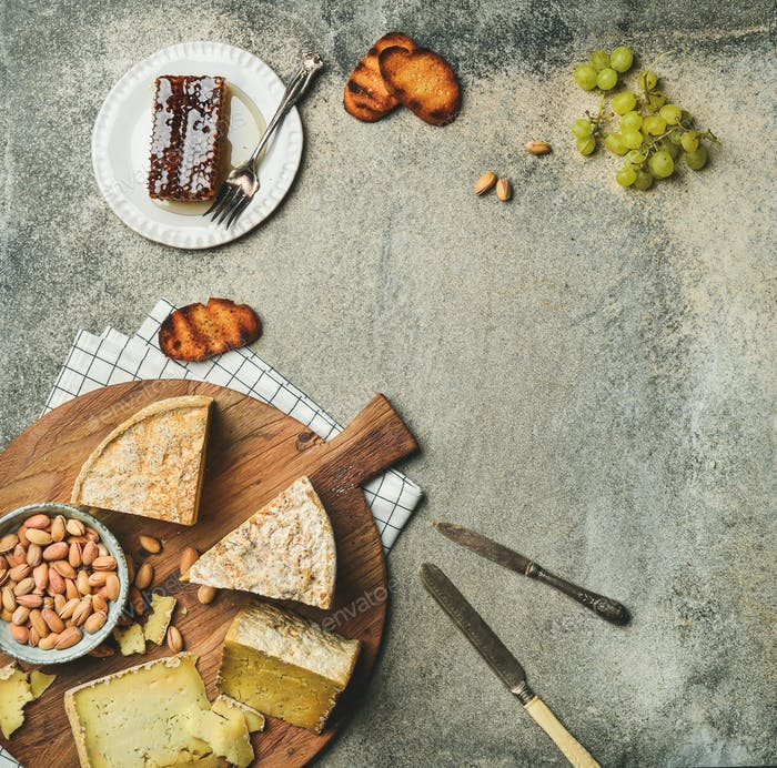 Flat-lay of platter with cheese assortment and snacks, copy space