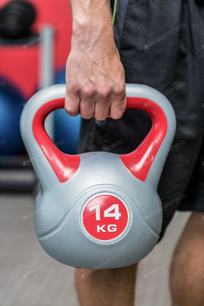 Close up view of a muscular man lifting a kettlebell