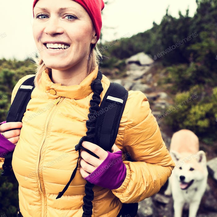 Happy woman hiking in vintage mountains with dog
