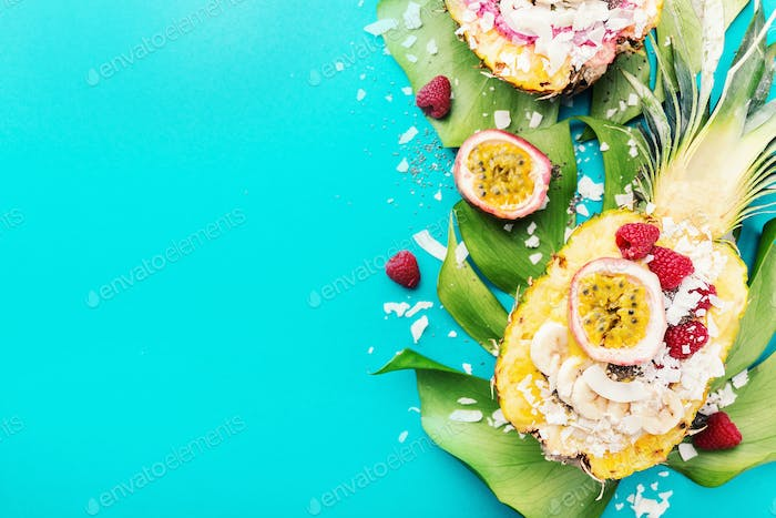 Smoothie bowls served in cut pineapple on blue