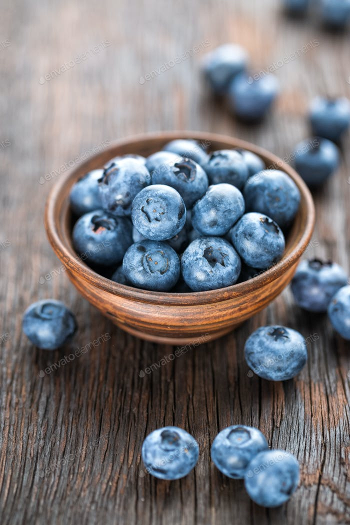 Fresh Blueberry in bowl on wooden background, closeup