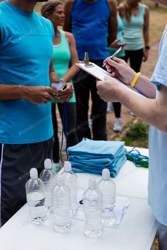 Thumbnail for Volunteer registering athletes name for race