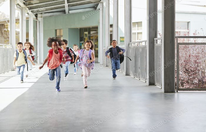 Elementary school kids running to camera in school corridor