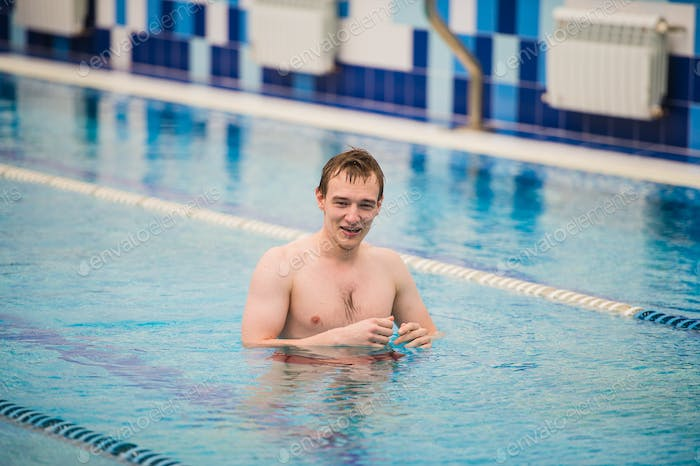 Young happy man in the swimming pool gesturing thumb up