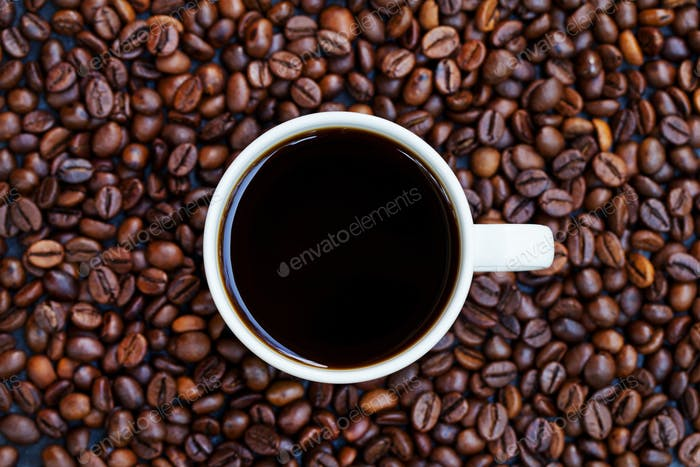Black Coffee in White Cup on Freshly Roasted Coffee Beans Background. Top View. Copy Space.