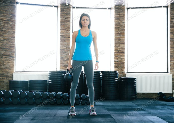 Beautiful young woman working out with kettle ball