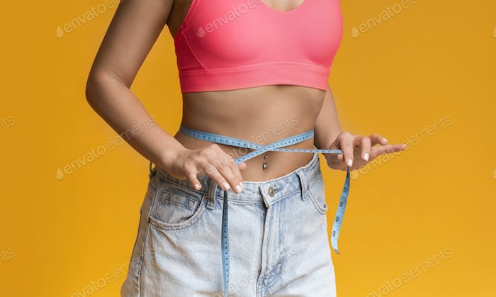 Unrecognizable Fit Female Measuring Waist With Measure Tape Over Yellow Background
