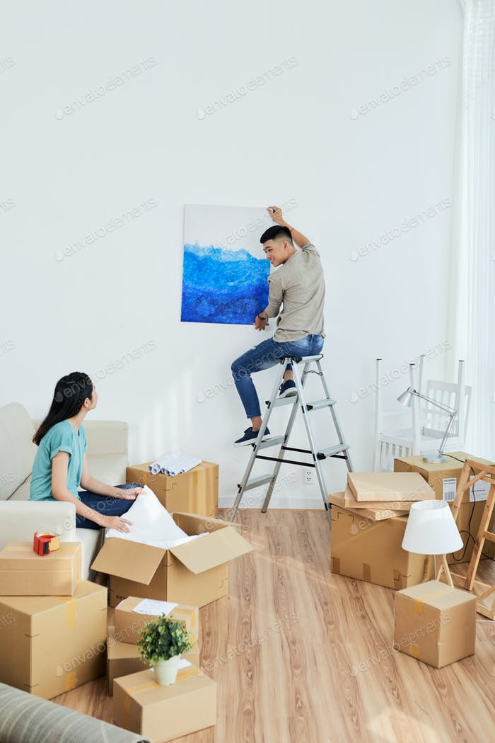 Young couple decorating new apartment