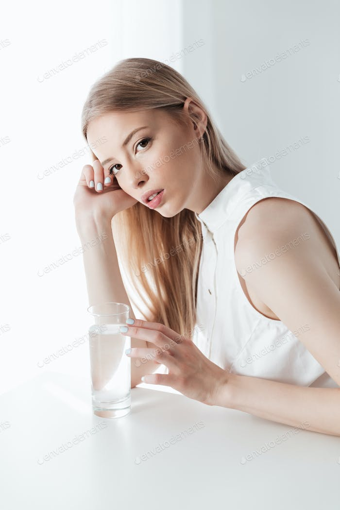 Serious blonde lady sitting indoors dressed in white dress