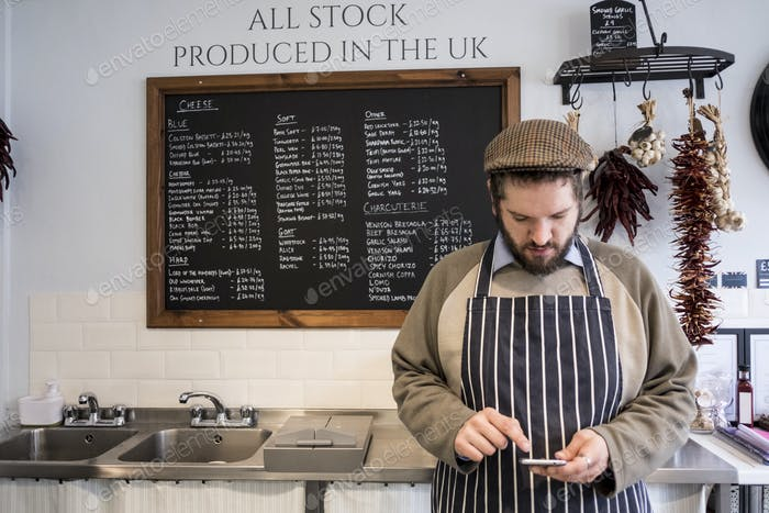 Store owner in a delicatessen using a digital tablet.