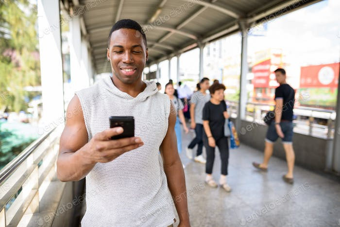 Happy young handsome African man using phone at the footbridge
