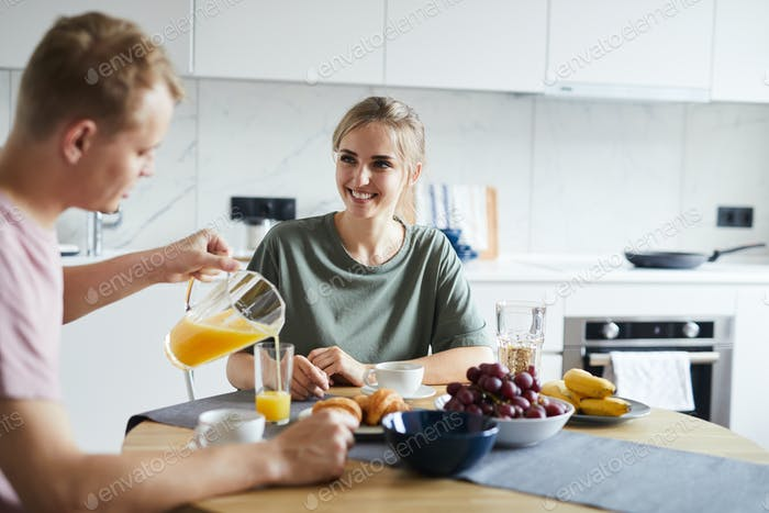 Young man pouring fresh orange juice in glass of his wife at breakfast