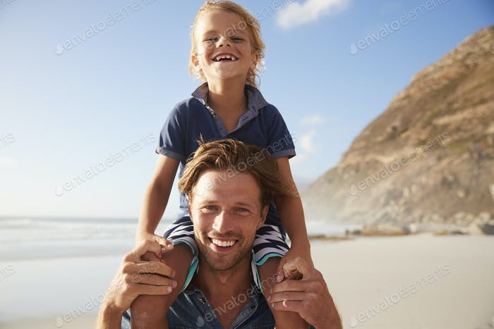 Portrait Of Father Carrying Son On Shoulders On Beach Vacation