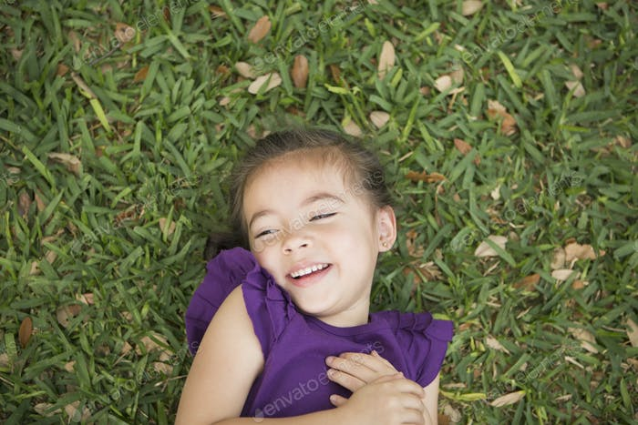 A child lying on her back on the grass.