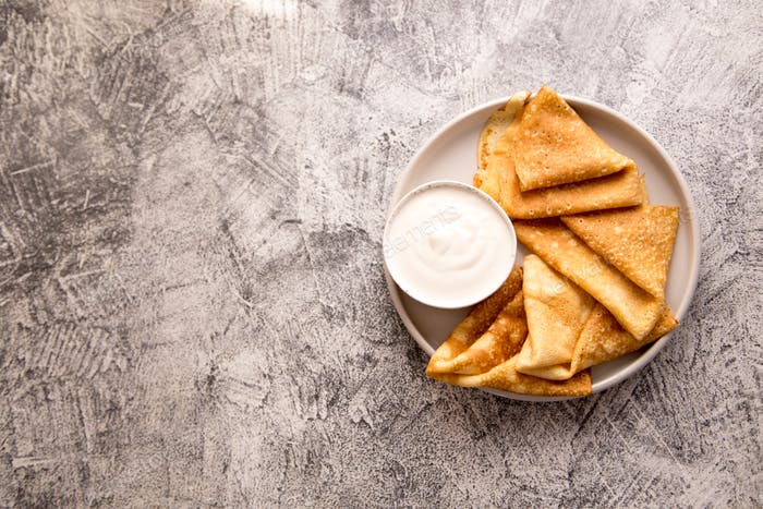 Traditional Russian pancakes. Fried crepes with sour cream