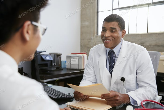 Mixed race male doctor holding documents in patient meeting