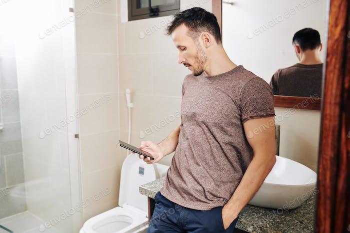 Man with smartphone hiding in bathroom
