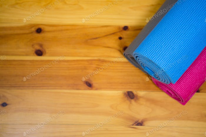 Rolled-up exercise mat on wooden floor