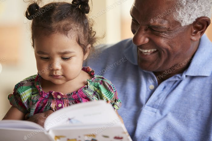 Grandfather Sitting On Sofa At Home With Baby Granddaughter Reading Book Together