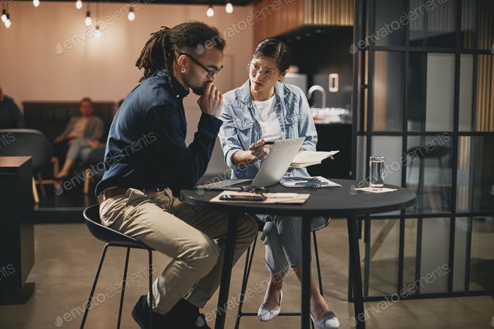 Two diverse young businesspeople working together at an office table