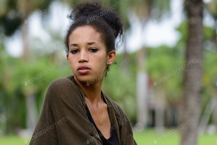 Portrait of young beautiful African woman at the park outdoors