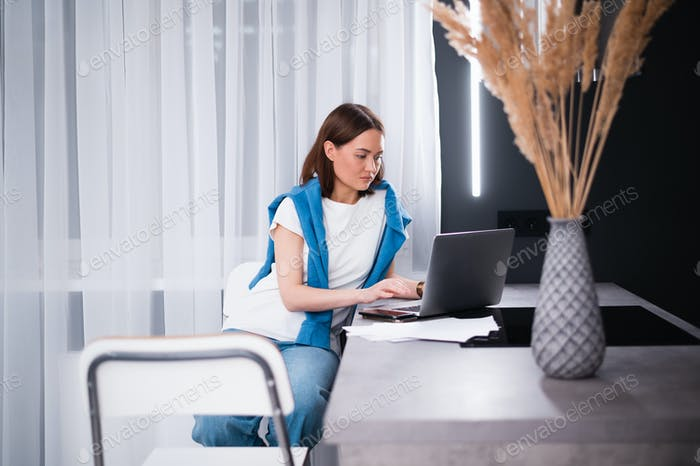 Focused young woman working on small business start up with a laptop. She is sitting at her kitchen