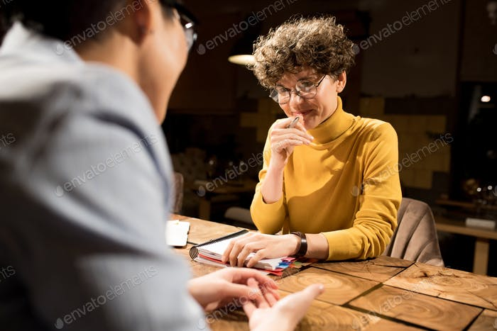 Content lady smirking while talking to colleague