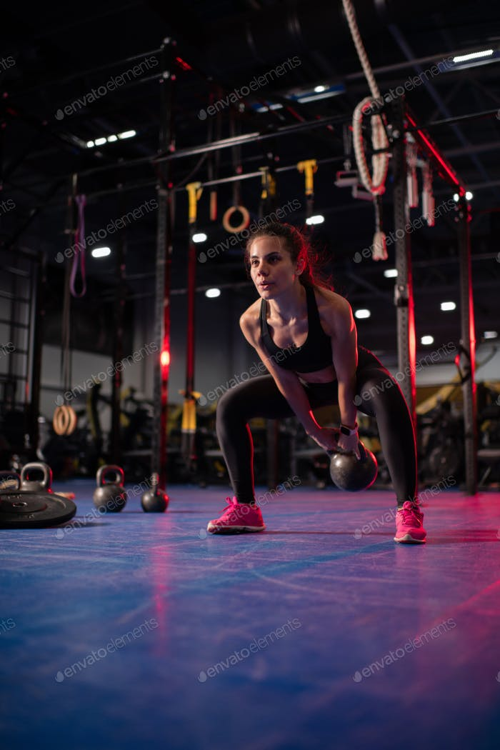 Strong sportswoman squatting and swinging kettlebell