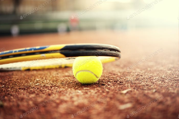 close-up of tennis ball and racket on clay court, summer day at tennis court