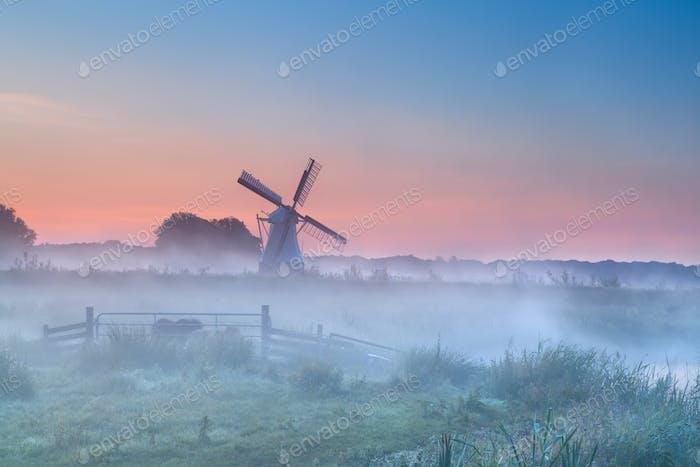 Molino de viento holandés en densa niebla de la mañana