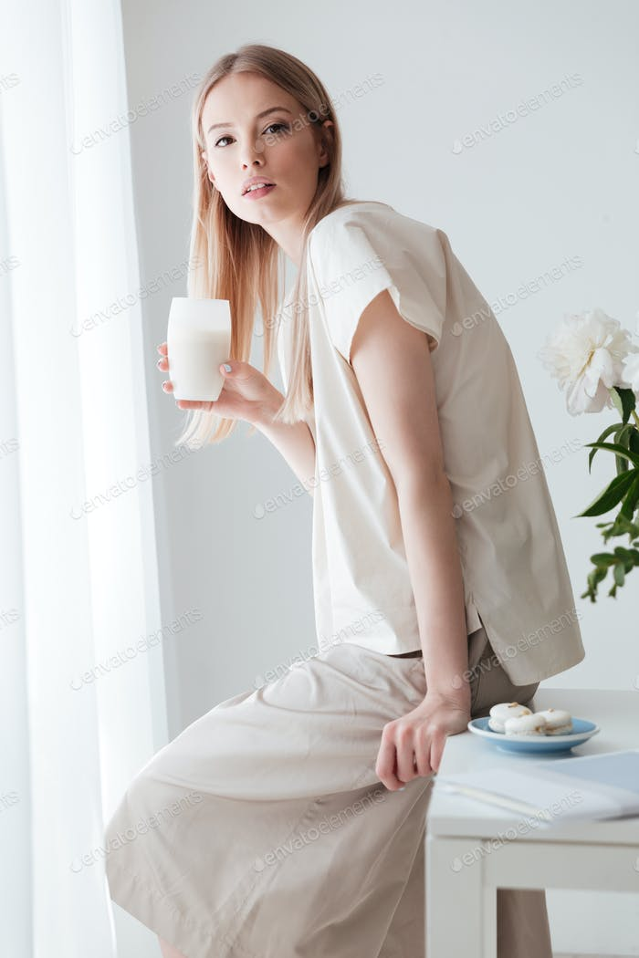 Serious woman sitting on table indoors drinking coffee